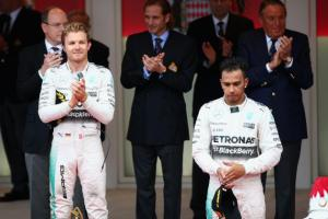 Nico Rosberg claps after his third-consecutive Monaco GP win as teammate Lewis Hamilton stands despondent.